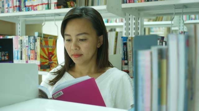 stockvideo's en b-roll-footage met uitvoerend vrouw in bibliotheek - auteur