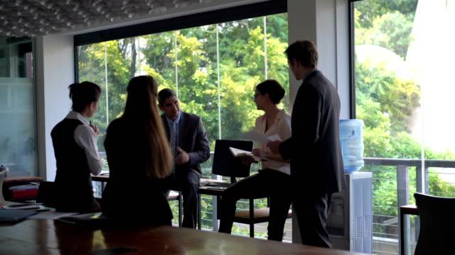 vidéos et rushes de executives communicating in modern office - tenue d'affaires formelle