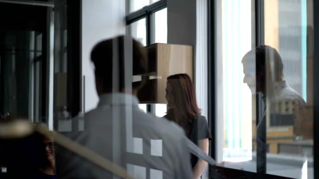 vidéos et rushes de executives seen through glass wall in office - reflet