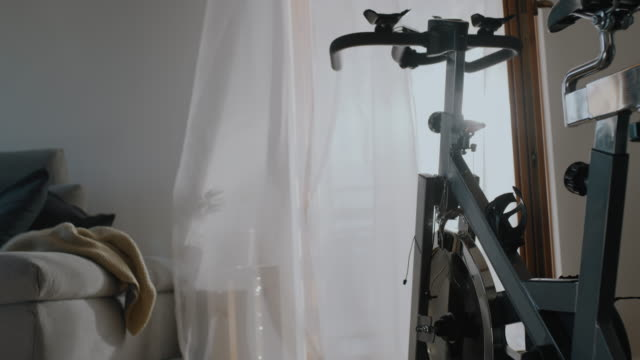 slo mo exercise bike in the living room - exercise room stock videos & royalty-free footage