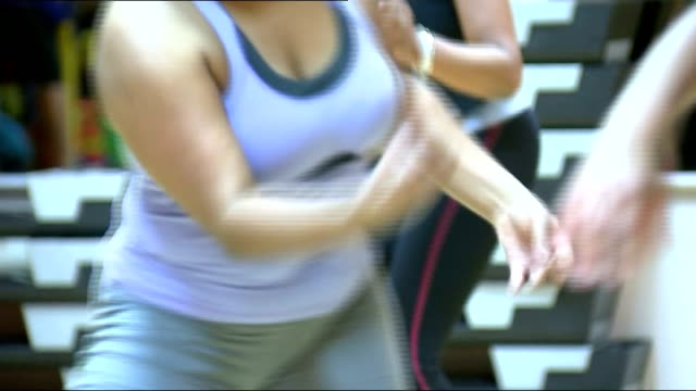 stockvideo's en b-roll-footage met exercise class and gym; england: birmingham: int ** music throughout zumba class *** women taking part in zumba exercise class / woman leading class... - vrijetijdsfaciliteiten