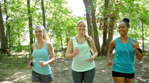 vidéos et rushes de club de sport marche rapide ensemble à l'extérieur sur la terre trail - public park