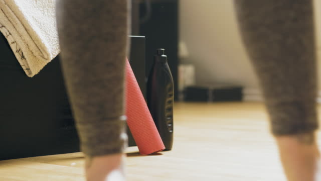 exercise mat and water bottle next to a woman exercising at home - barefoot stock videos & royalty-free footage