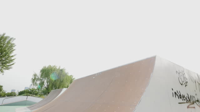 vidéos et rushes de exercise - young person skateboarding at skate park in city - glisser