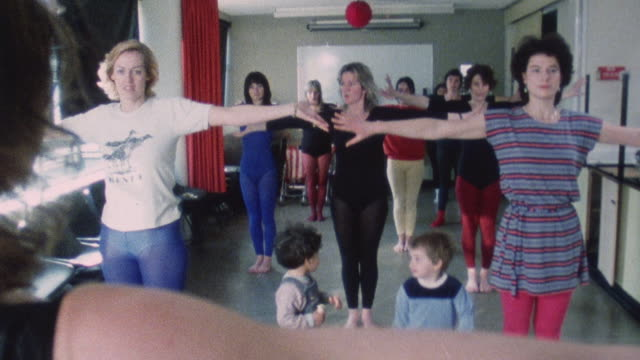 1983 MONTAGE Exercisers working out in class setting while a few children run about / London, England