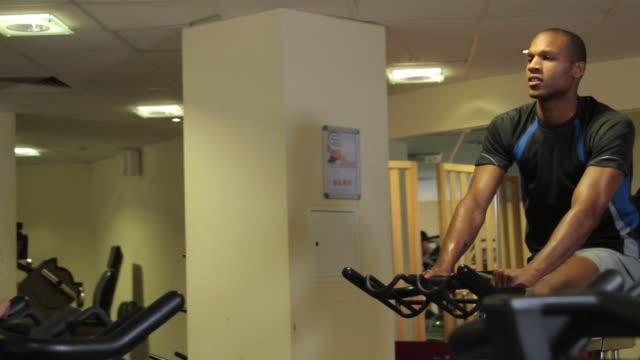 exercising class with male coach in gym - インドアサイクリング点の映像素材/bロール