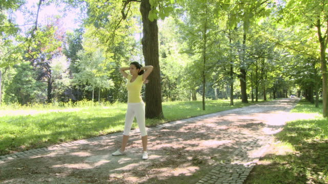 hd crane: exercising in the park - hands behind head stock videos and b-roll footage