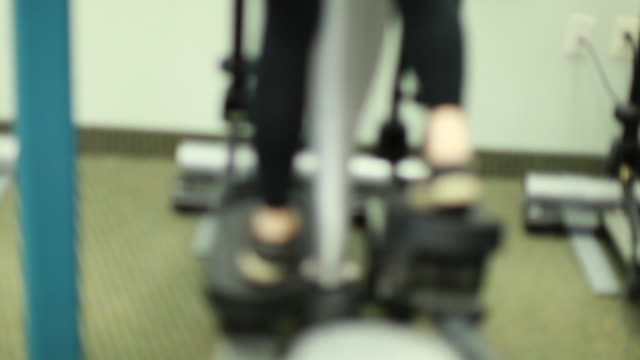 exercising on an elliptical machine - exercise machine stock videos & royalty-free footage