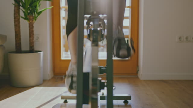 slo mo exercising on the exercise bike at home - exercise bike stock videos & royalty-free footage