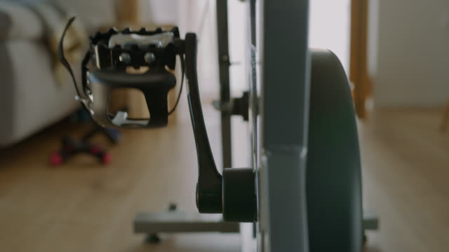 slo mo spinning pedals on the exercise bike in a cozy living room - exercise room stock videos & royalty-free footage
