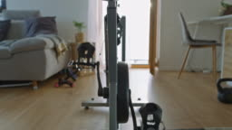 SLO MO exercising pedals on the exercise bike in a cozy living room