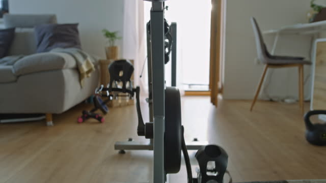 slo mo spinning pedals on the exercise bike in a cozy living room - pedal stock videos & royalty-free footage