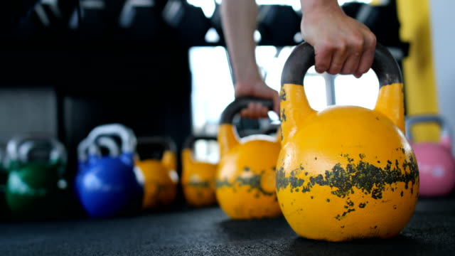 Exercising with kettle bell in the gym