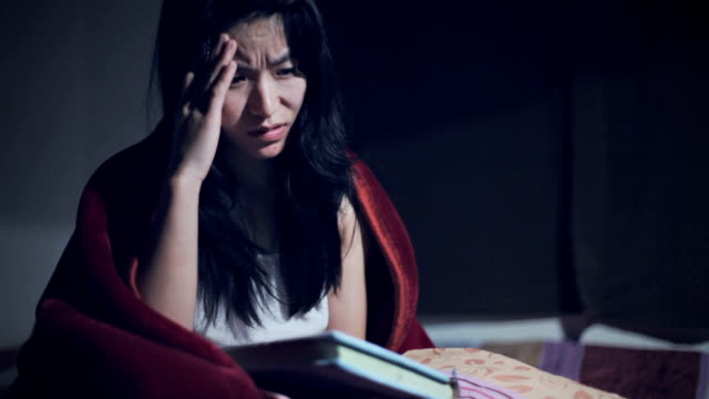 exhausted asian college student studying late night at home. - coprire video stock e b–roll