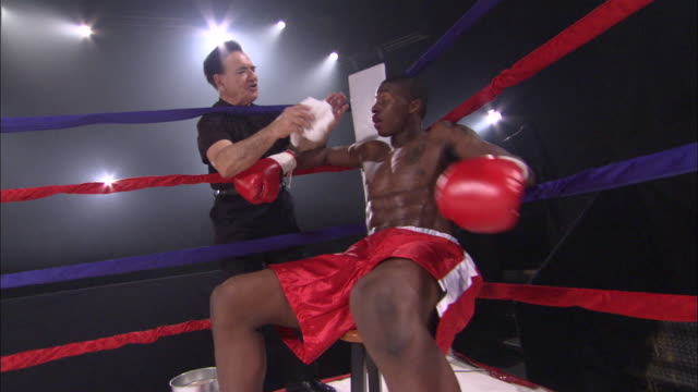 vidéos et rushes de sm la ms exhausted, bloody boxer sitting down in corner while coach talks to him before throwing towel into ring / jacksonville, florida, usa - ring de boxe