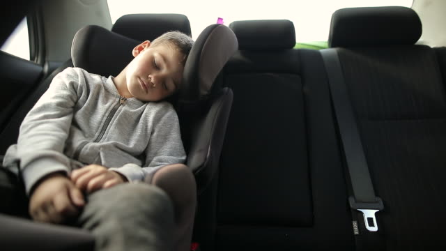 exhausted boy in car safety seat sleeping during road trip during vacation - one boy only stock videos & royalty-free footage