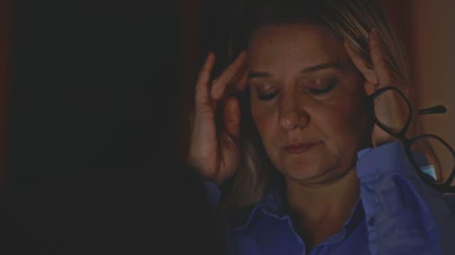 vidéos et rushes de femme d'affaires épuisée de ms travaillant la nuit - trentenaire