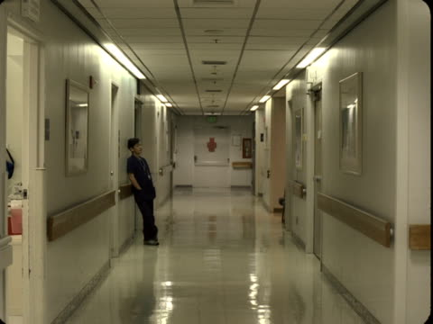 WS, Exhausted female doctor leaning against wall in hospital corridor, Reno, Nevada, USA