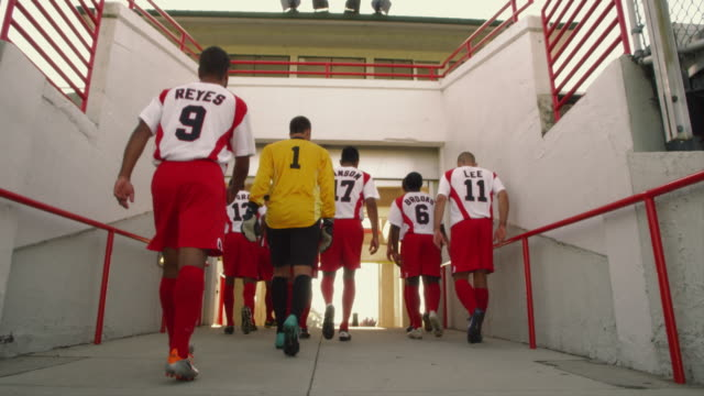 slo mo. exhausted group of athletic soccer players slowly walk up the entrance ramp of a stadium at the end of a match - medium group of people stock videos & royalty-free footage