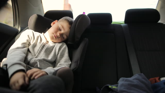 exhausted little kid in car safety seat sleeping after fun weekend activities - back seat stock videos & royalty-free footage