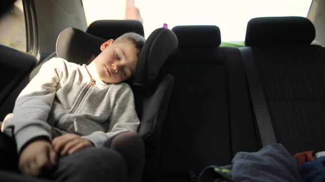 vídeos y material grabado en eventos de stock de niño agotado en el asiento de seguridad del coche durmiendo después de las actividades divertidas del fin de semana - asiento de atrás