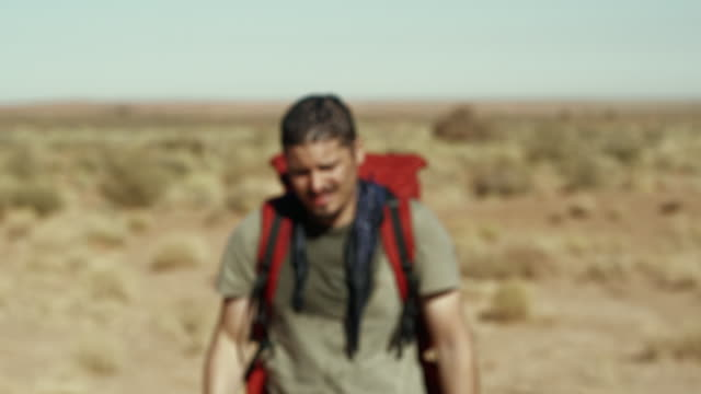 vidéos et rushes de ms, cu, focusing , exhausted man walking through monument valley, arizona, usa - hot