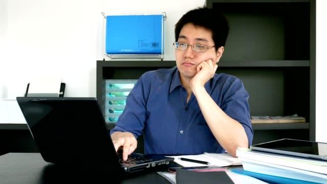 mann mit brille erschöpft arbeiten auf laptop-computer zu hause - home office konzept - erschöpfung stock-videos und b-roll-filmmaterial