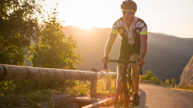 Exhausted road cyclist cycling uphill at sunset