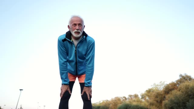 exhausted senior man taking a break from jogging - exhaustion stock videos & royalty-free footage