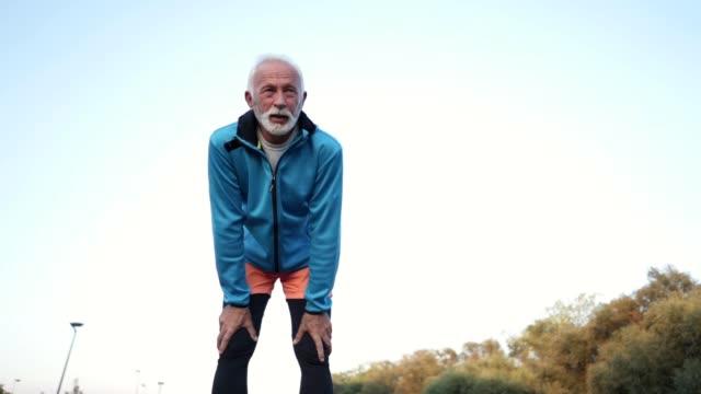 vidéos et rushes de homme senior épuisée, prenant une pause du jogging - marathon
