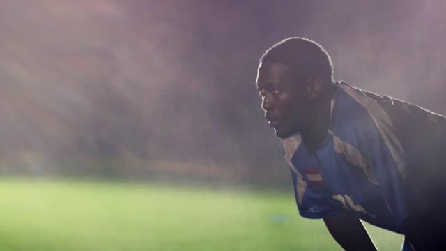 slo mo. exhausted soccer player bends over to catch his breath on a soccer field during a nighttime match - defender soccer player stock videos and b-roll footage