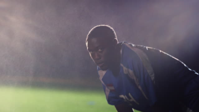 slo mo. exhausted soccer player bends over to catch his breath on a soccer field during a nighttime match - schmutzig stock-videos und b-roll-filmmaterial