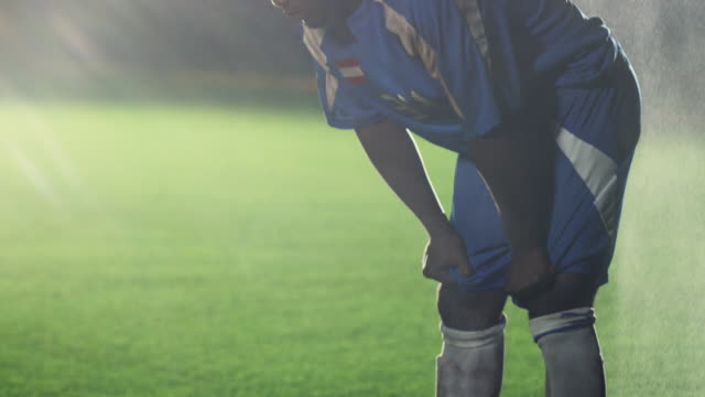 slo mo. exhausted soccer player bends over to catch his breath then walks further down the soccer field during a nighttime match - exhaustion stock videos & royalty-free footage