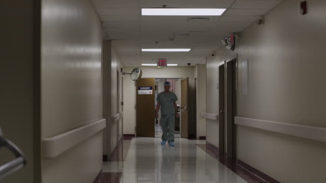 vidéos et rushes de ws td exhausted surgeon exiting operation room and resting in hospital corridor / payson, utah, usa - payson