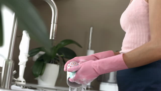 hd: exhausted woman doing the dishes - rubber glove stock videos & royalty-free footage