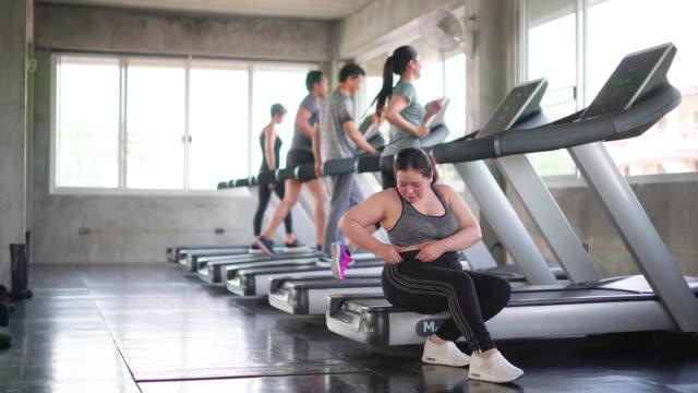 vidéos et rushes de femme épuisé s'asseyant sur des tapis roulants - entraînement cardiovasculaire