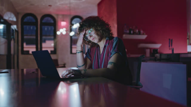 vídeos de stock, filmes e b-roll de exhausted woman takes a break from her laptop as she works late into the night - atormentado