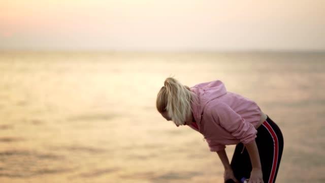 疲れ果てた女性はジョギングから休憩を取った - resting点の映像素材/bロール