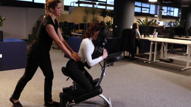 vídeos de stock e filmes b-roll de exhausted young business woman enjoying back massage after long hard working office day - dor no pescoço