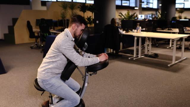 vídeos de stock e filmes b-roll de exhausted young entrepreneur sitting on a portable massage chair - dor no pescoço