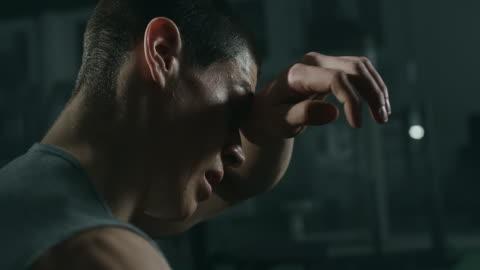 utmattad ung man koncentrera sig mellan serien i gymmet - svett bildbanksvideor och videomaterial från bakom kulisserna