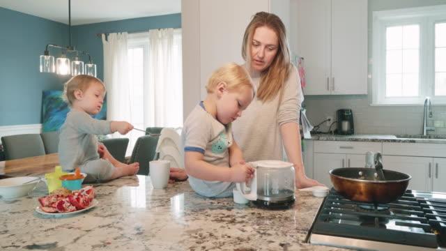 疲れ果てた朝のルーチン - キッチンで朝食を食べる彼女の子供とシングルマザー - 生後18ヶ月から23ヶ月点の映像素材/bロール