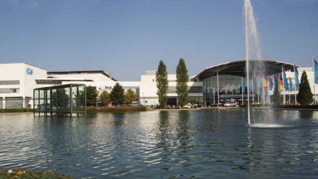 ws, pan, exhibit hall entrance across pond, munich, germany - messen stock-videos und b-roll-filmmaterial