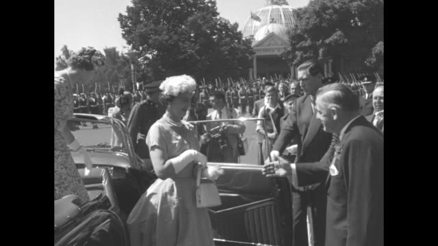 exhibition emblems flags / duchess of kent princess marina and daughter princess alexandra arrive in cadillac convertible / they step out of car... - cadillac stock videos & royalty-free footage