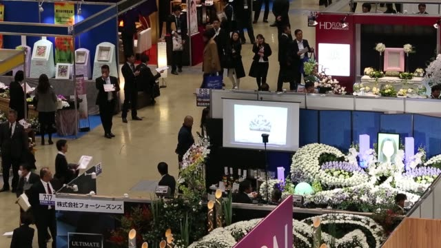Exhibitor booths stand at the Life Ending Industry Expo in Tokyo Japan on Tuesday Dec 8 Attendees walk past exhibitor booths Balloons for space...