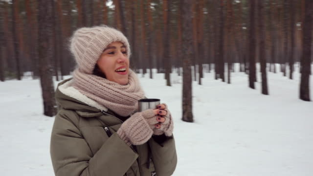 exhilarated woman getting warm with tea on a cold day in the forest - mitten stock videos and b-roll footage