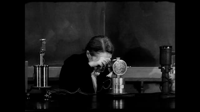 exiled austrian physicist lise meitner looking into machine on desk. - esilio video stock e b–roll