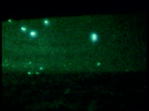 exiles in britain give opinions; pool lib from server night 1991 green nightscope shot anti aircraft fire in night sky over baghdad - バグダッド点の映像素材/bロール