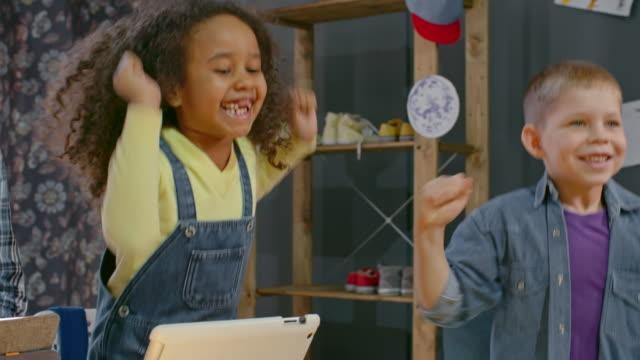 vídeos de stock, filmes e b-roll de exited kids watching robots and jumping - stem assunto