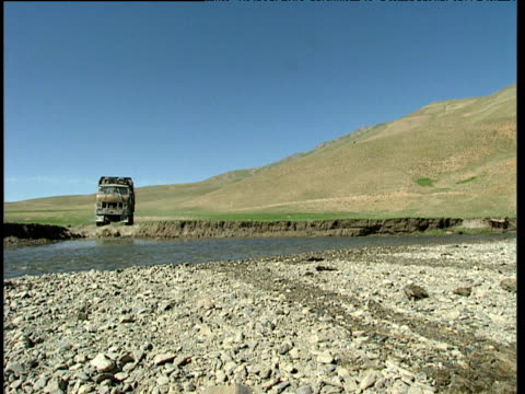 exmilitary lorry transports opium workers across shallow river in barren mountainous landscape afghanistan - landscape scenery点の映像素材/bロール